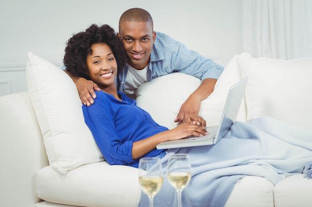 テーブルの上の白ワインのグラスとラップトップを使用してソファの上の幸せなカップル