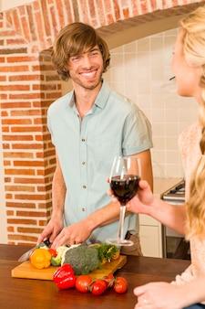 かわいいカップルのワインを楽しんで、キッチンで野菜をスライス