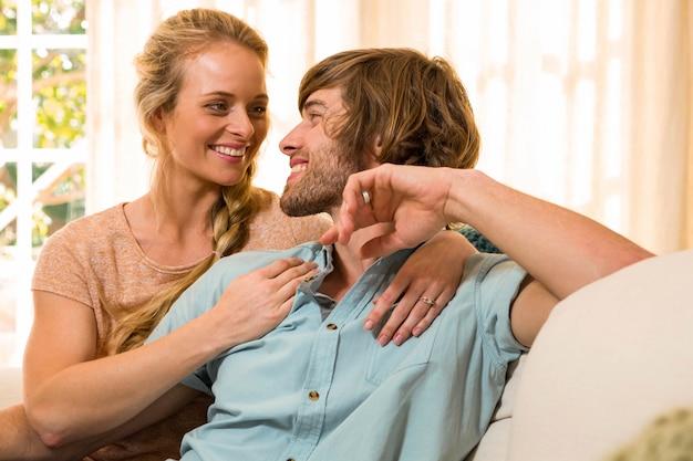 かわいいカップルを抱き締めると、リビングルームのソファで休む