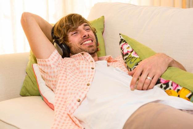 ソファに横になっているヘッドフォンで音楽を聞いているハンサムな男