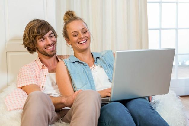 リビングルームのソファに座ってラップトップを使用してかわいいカップル