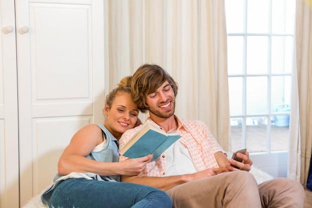 かわいいカップルは本を読んで、リビングルームでスマートフォンを使用して