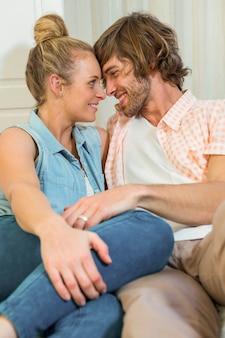 かわいいカップルが愛情を込めてリビングルームでお互いを見て