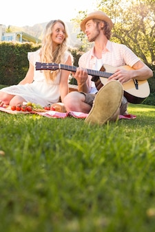幸せなカップルのピクニックと庭でギターを弾く