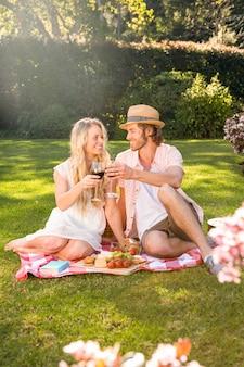 庭でピクニックと飲み物の赤ワインを持っている幸せなカップル