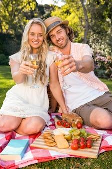 庭でピクニックとドリンクシャンパンを持っている幸せなカップル
