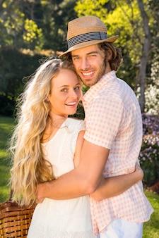 庭でピクニックバスケットを保持しているカップルの背面図
