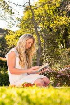 庭で読書草の上に座って美しいブロンド