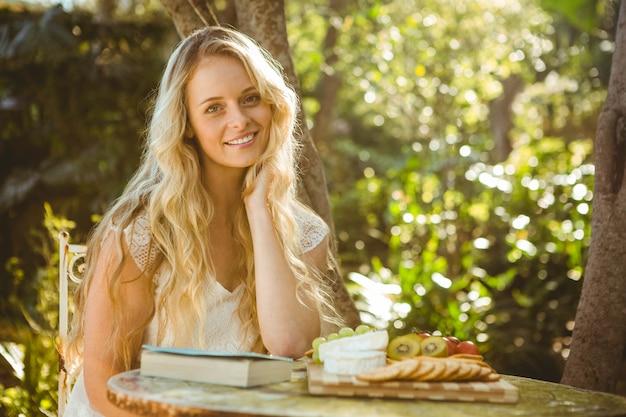 Красивая блондинка отдыхает с книгой и едой в саду