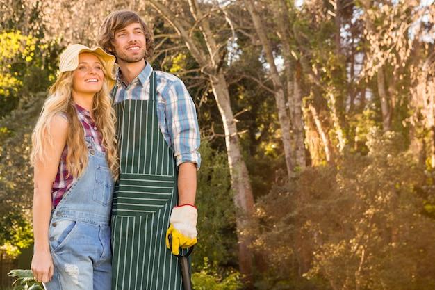 シャベルを保持している庭で笑顔のカップル