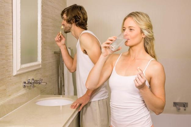 自宅の浴室で彼の歯を磨く彼女のボーイフレンドと一緒にピルを服用しているブロンドの女性