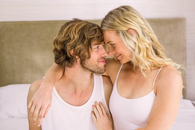 かわいいカップルが自宅のベッドで頭を抱きしめる