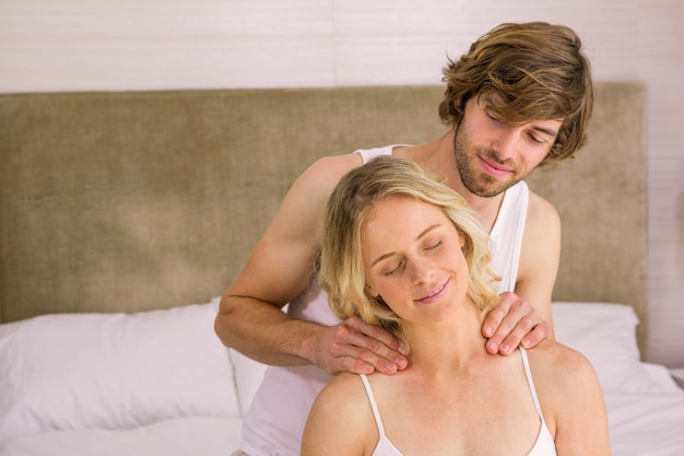 自宅の寝室で彼のガールフレンドにマッサージを与えるボーイフレンド