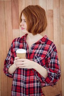 コーヒーカップを保持している美しい流行に敏感な女性