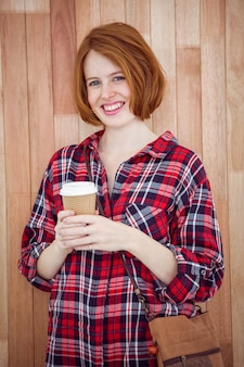コーヒーカップを保持している笑顔の流行に敏感な女性