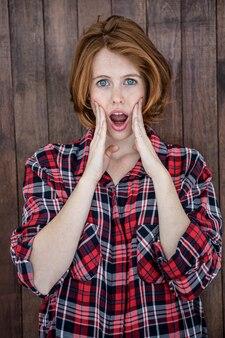 木製のカメラに探しているショックを受けた流行に敏感な女性