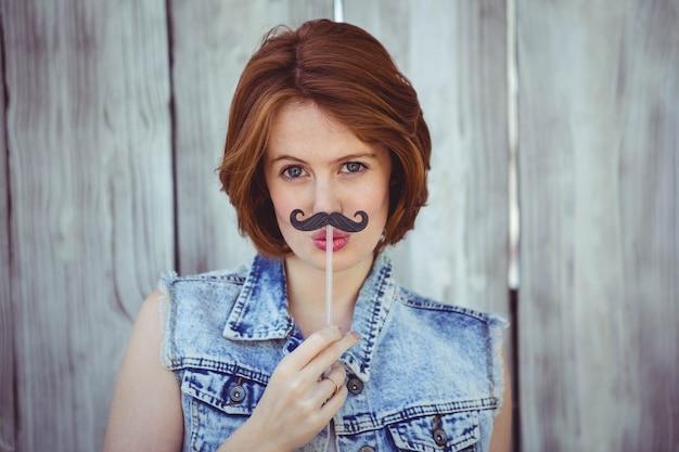 彼女の顔に偽の口ひげを保持している美しい流行に敏感な女性