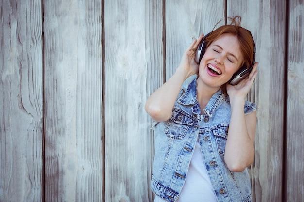 笑みを浮かべて流行に敏感な女性彼女の耳をカッピング、ヘッドフォンで大声で音楽を聴く