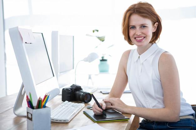 彼女のオフィスでデジタル描画タブレットに書いて笑顔の流行に敏感な実業家