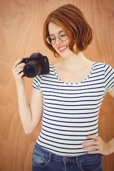 デジタルカメラを保持している笑顔の流行に敏感な女性