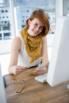 笑顔の流行に敏感なビジネス女性、彼女の机に座って、色見本を見て