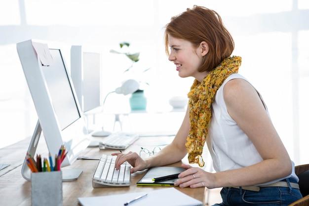 流行に敏感なビジネス女性の笑みを浮かべて、彼女の机に座って、彼女のコンピューターに入力します。