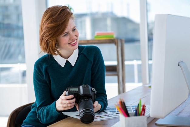笑顔の流行に敏感な写真家、彼女の机に座って、彼女のカメラを見て