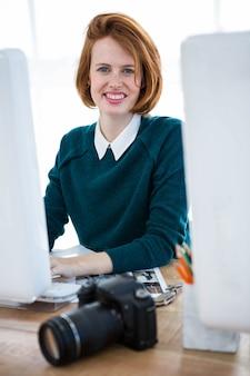 彼女のコンピューターで彼女の机に座っている笑顔の流行に敏感な写真家
