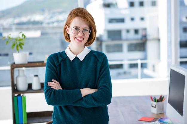 Деловая женщина улыбается битник, стоя в ее офисе со сложенными руками