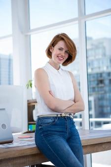 腕を組んで彼女のオフィスに立っている笑顔の流行に敏感なビジネス女性