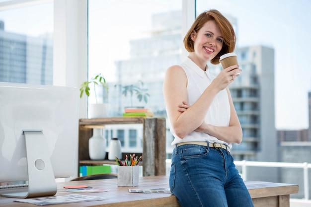 流行に敏感なビジネス女性の笑みを浮かべて、彼女の机にもたれて、コーヒーを飲む