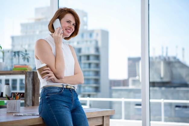 コーヒーカップを保持していると電話をかける流行に敏感なビジネス女性の笑みを浮かべてください。