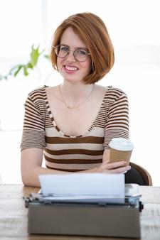 タイプライターの前に座って、コーヒーカップを保持している笑顔の流行に敏感な女性