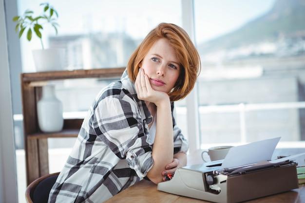 流行に敏感な女性彼女の机に座って、思考と彼女のタイプライターで入力