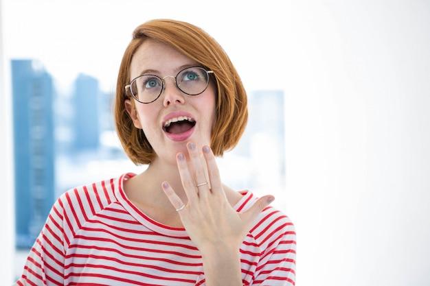 窓の前で眼鏡をかけたかわいい赤髪ヒップスター