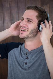 ヘッドフォンで音楽を聴くハンサムなヒップスター