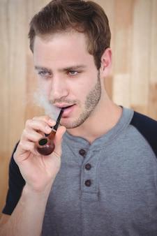 ハンサムなヒップスター喫煙パイプ