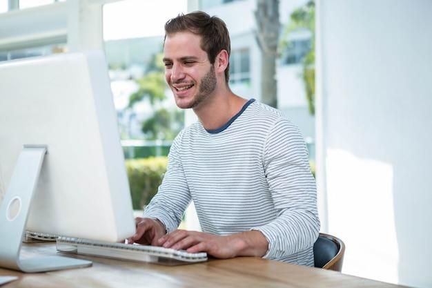 明るいオフィスでコンピューターに取り組んでいるハンサムなヒップスター