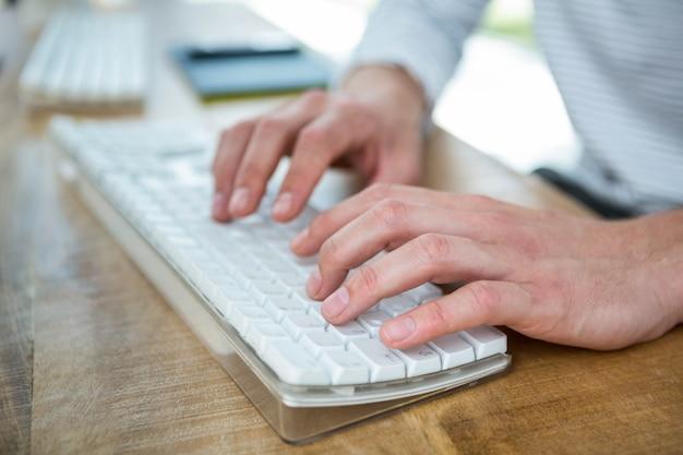 Мужские руки, набрав на клавиатуре в ярком офисе