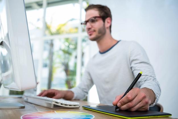 Красивый мужчина работает на компьютере и делать заметки в ярком офисе