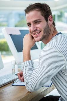コンピューターで作業し、明るいオフィスでメモを取るハンサムな男