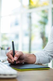 明るいオフィスでデジタルタブレットに書く男性の手