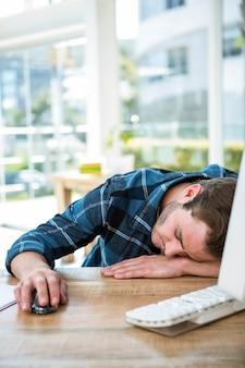 Красивый мужчина спит на компьютере в ярком офисе