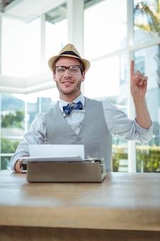 明るいオフィスで昔ながらのタイプライターを使用してハンサムな男