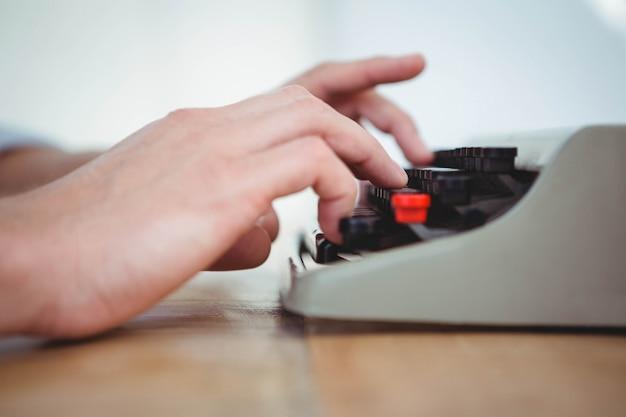 木製のテーブルに古いタイプライターで入力する男性の手