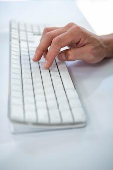 キーボードで入力する男性の手のクローズアップ表示