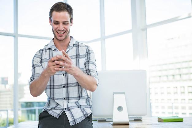 オフィスでスマートフォンを使用して流行に敏感な男