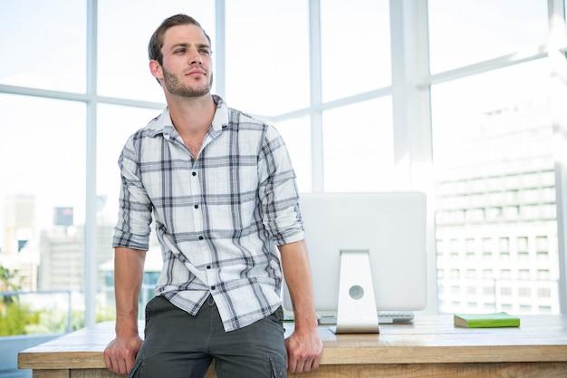 オフィスの机の上に座っている流行に敏感な男