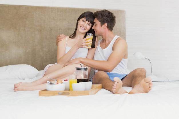 寝室で一緒に朝食をとりながら笑顔若いカップル