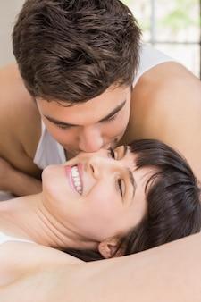 寝室のベッドの上の女性にキスをする男性